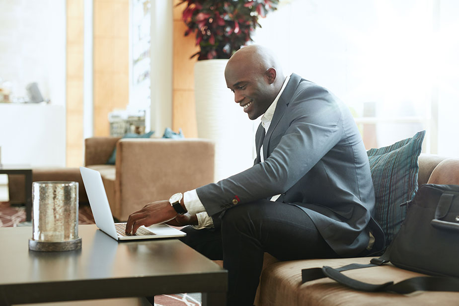 happy-businessman-using-laptop-in-hotel-lobby-african-business-executive-sitting-on-couch-at-hotel-lobby-working-on-his-laptop-and-smiling_Halt8r4tg